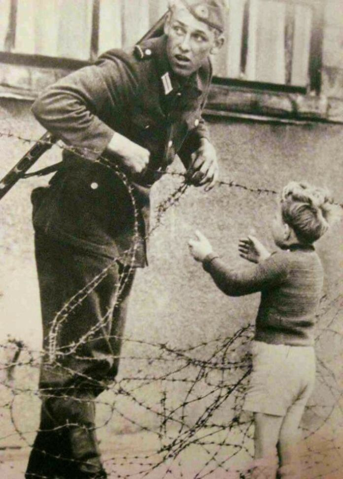 Incredible Photograph Of A German Soldier Going Against Direct Orders To Help A Young Boy Cross The Newly Formed Berlin Wall After Being Separated From His Family, 1961