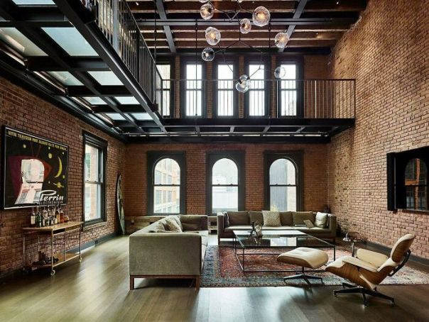 Living Area With Lots Of Exposed Brick Sits Beneath A Metal Catwalk In This Loft In New York City