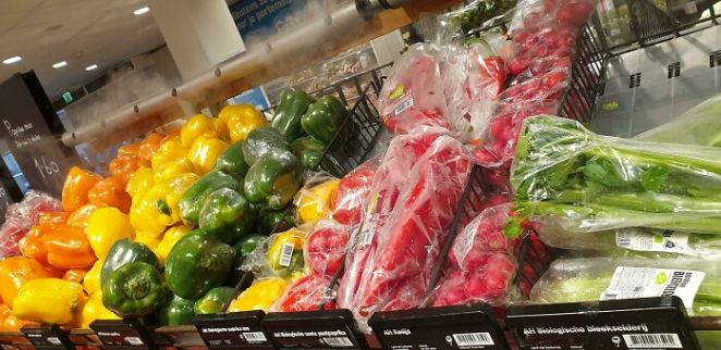 Spraying Water Over Vegetables Wrapped In Plastic, Complete Waste