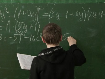 The image above shows a student working on equations on a blackboard.