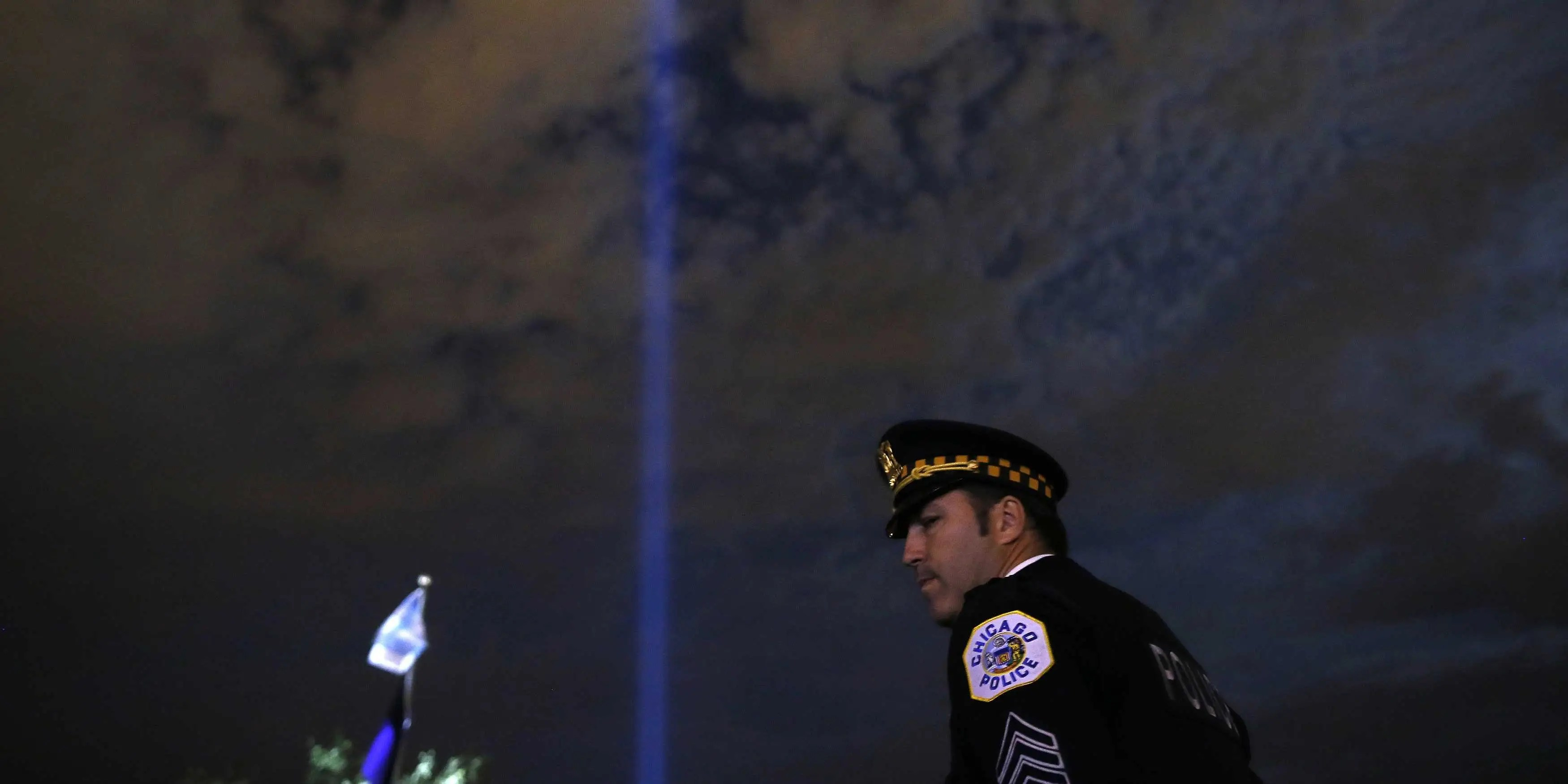 A police officer stands beneath a beam of light projected into the sky at the 10th Annual Chicago Police Memorial Foundation's Candlelight Vigil in Chicago, Illinois, September 17, 2013.