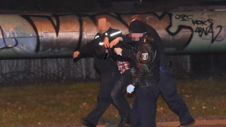 Ein Verdächtiger wird von der Polizei abgeführt