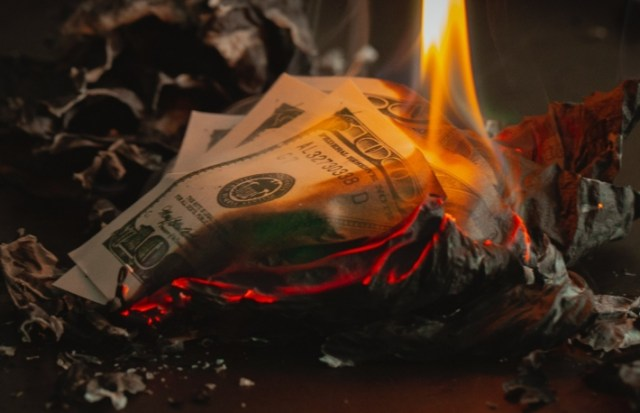 US $100 bills burning