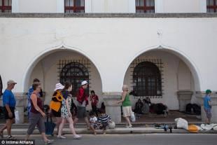 migranti in strada fra i turisti