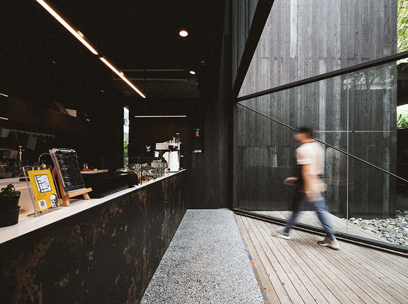 black timber cladding envelops IDIN architects' tranquil office space in bangkok designboom