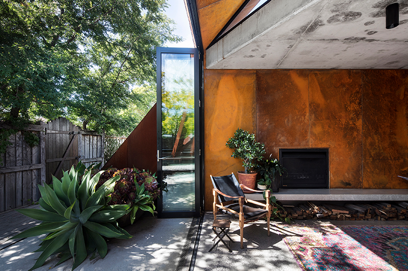angular corten roof folds down over leaf house extension in melbourne