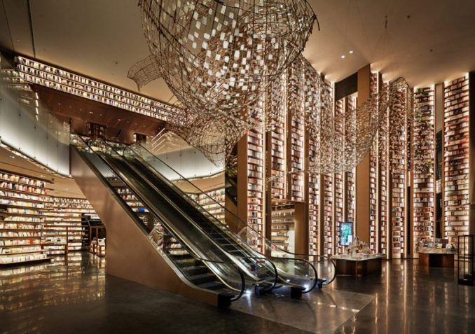 tomoko ikegai / ikg inc illuminates chinese bookstore with fluttering sheets of paper designboom