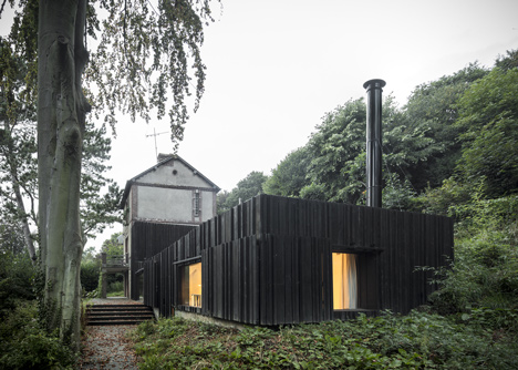 Blackened timber house extension in the forest by Marchi