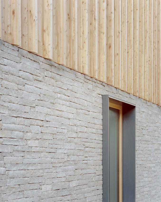 A stone and wood facade of an Italian chalet by LCA Architetti