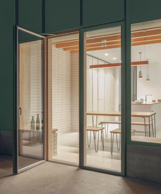 A kitchen inside a green aluminium-clad extension by DeDraft