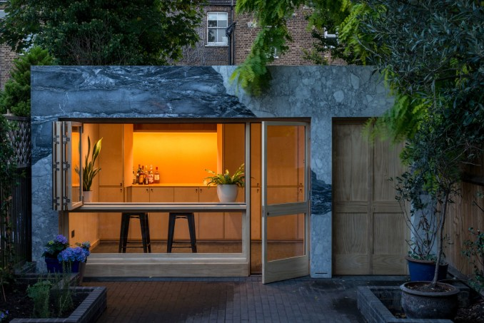 Marble-clad garden room of Hansler Road house extension by Alexander Owen Architecture at night