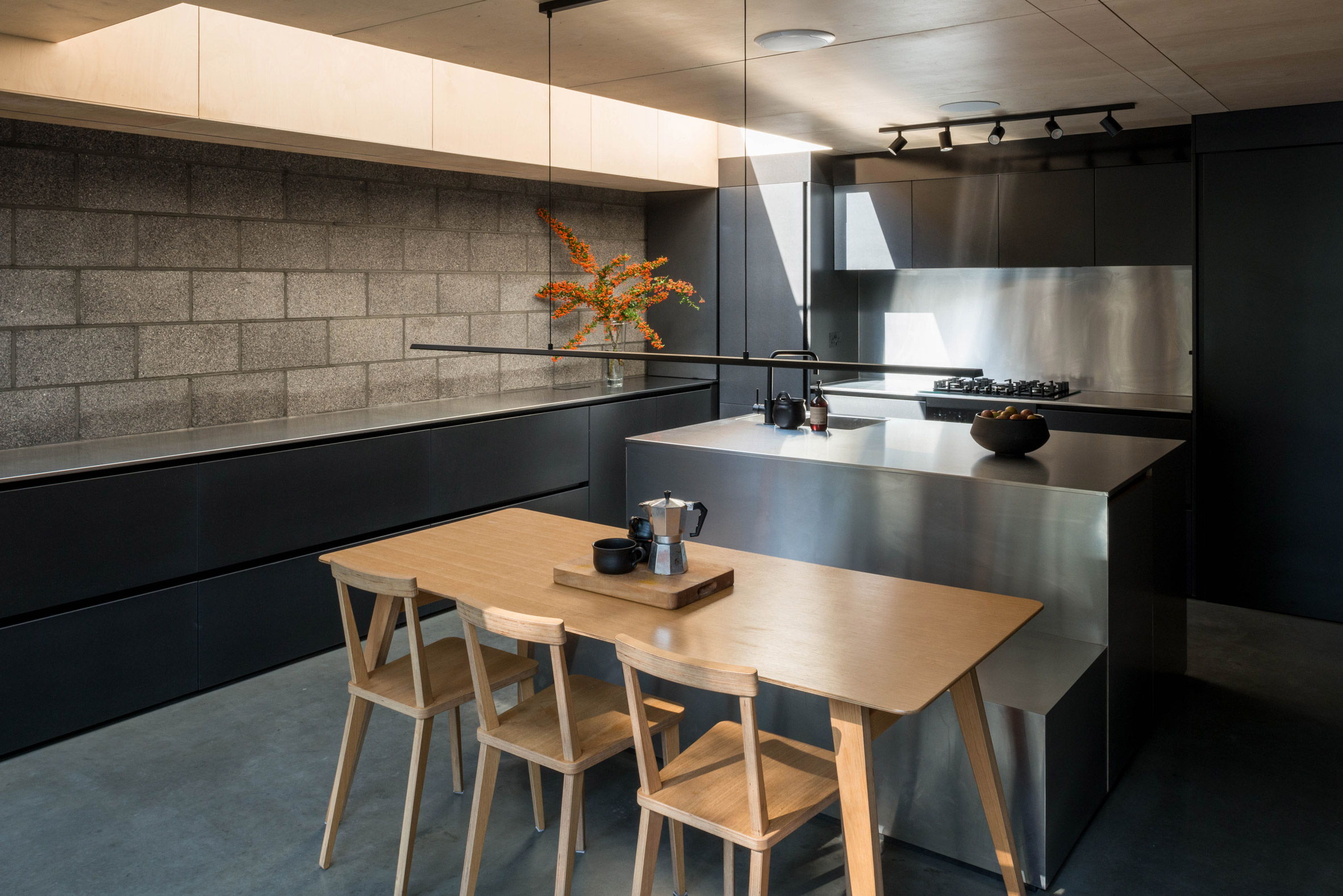 Stainless steel kitchen and pewter brick walls of Hansler Road house extension by Alexander Owen Architecture