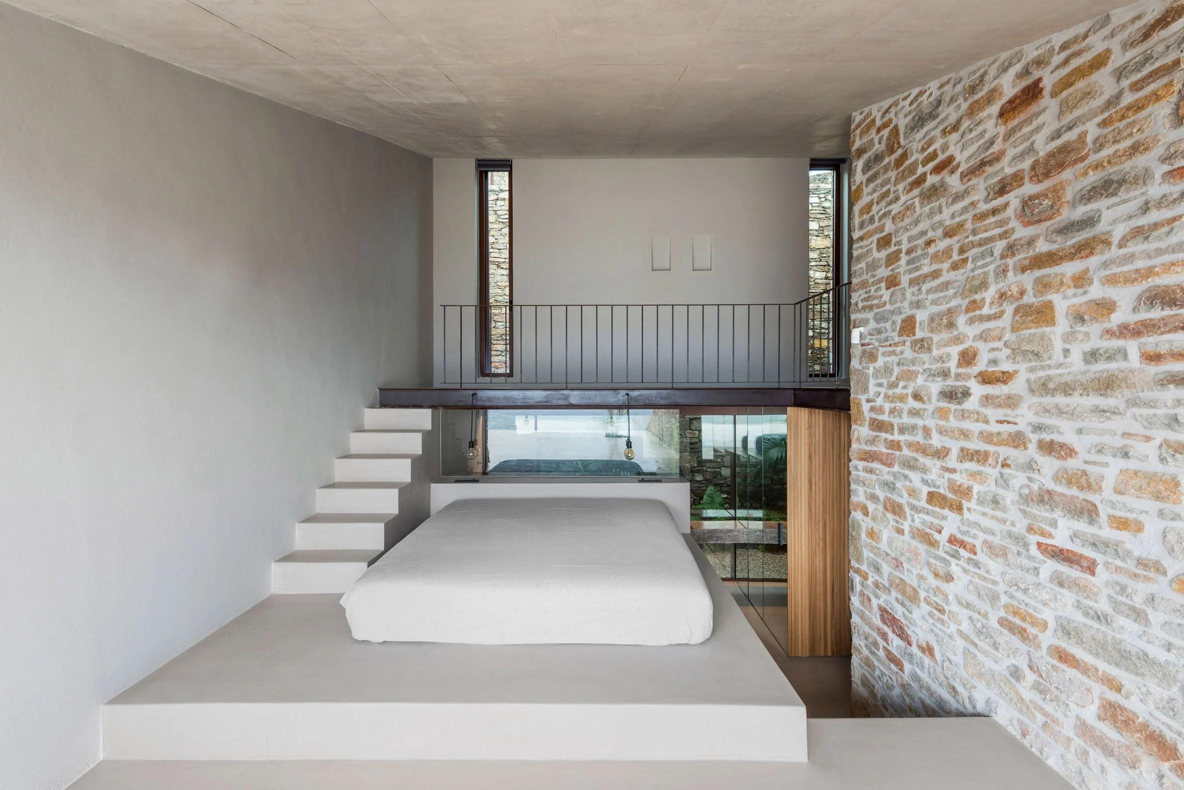 Split level bedroom features a platform bed and mezzanine
