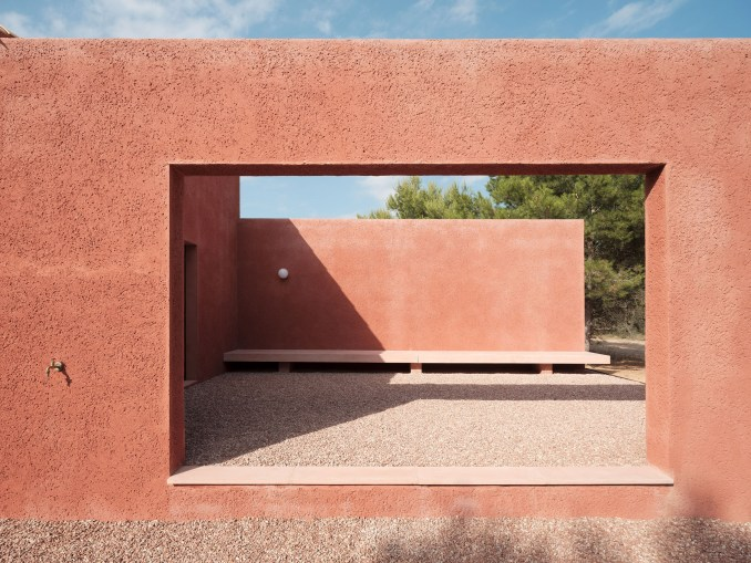 An opening in a facade covered in red-coloured mortar