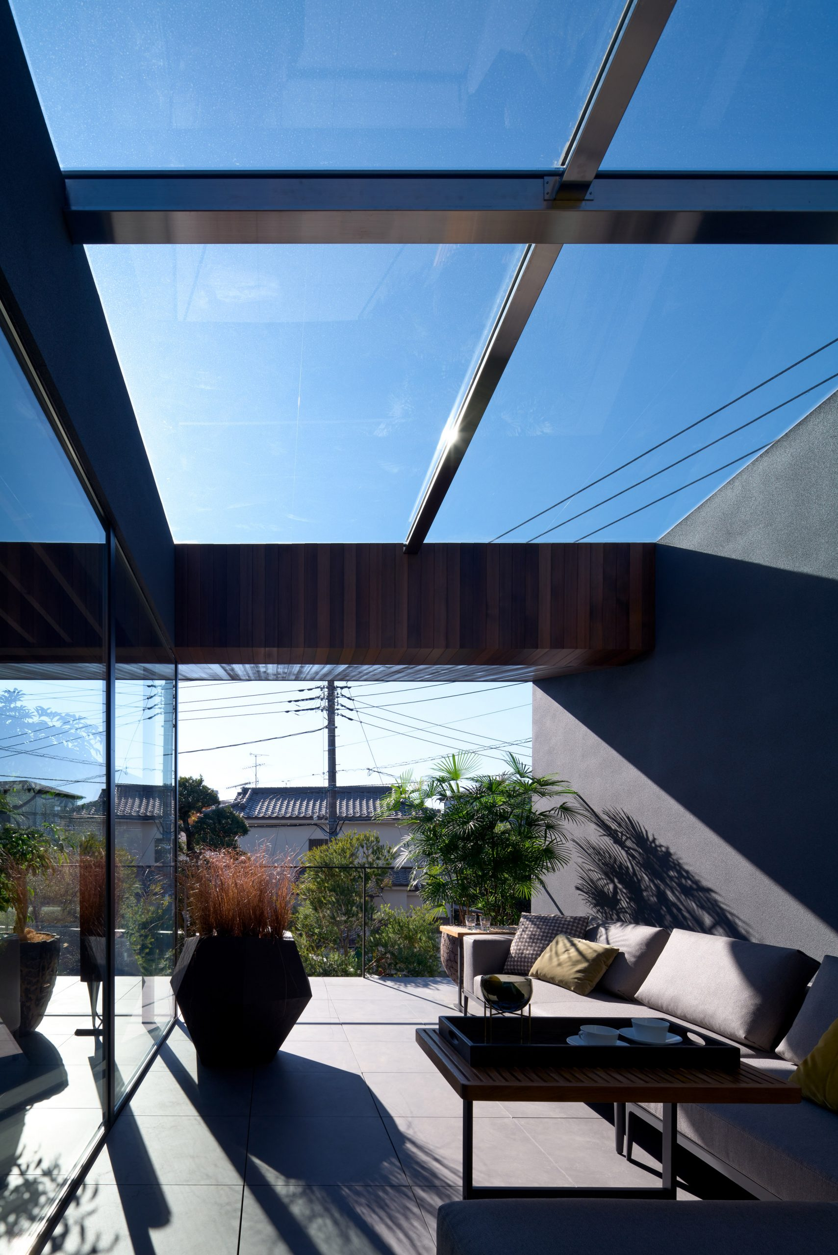 A terrace is covered by a glass roof by Apollo Architects & Associates