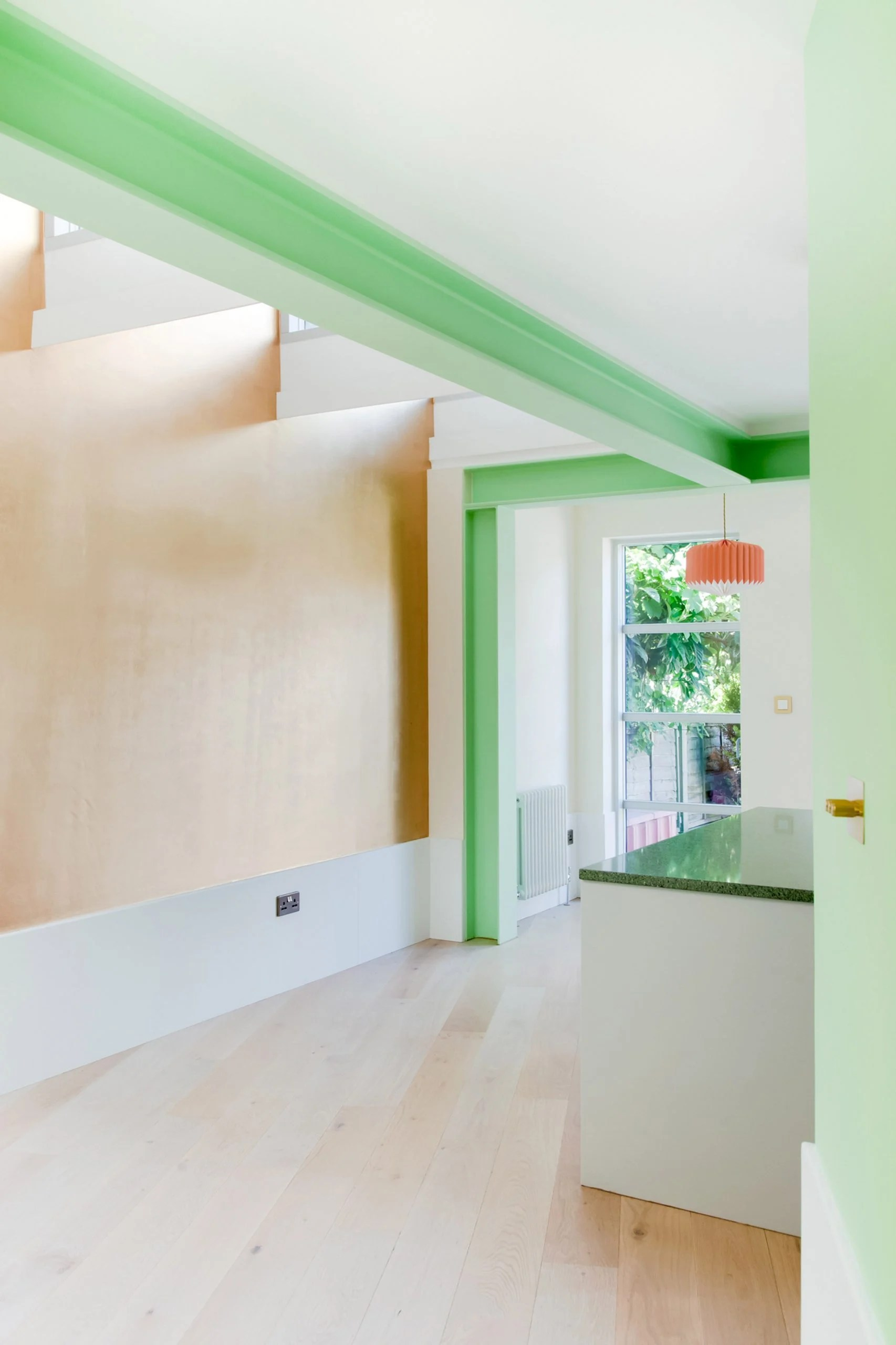 A light kitchen extension with green structural beams