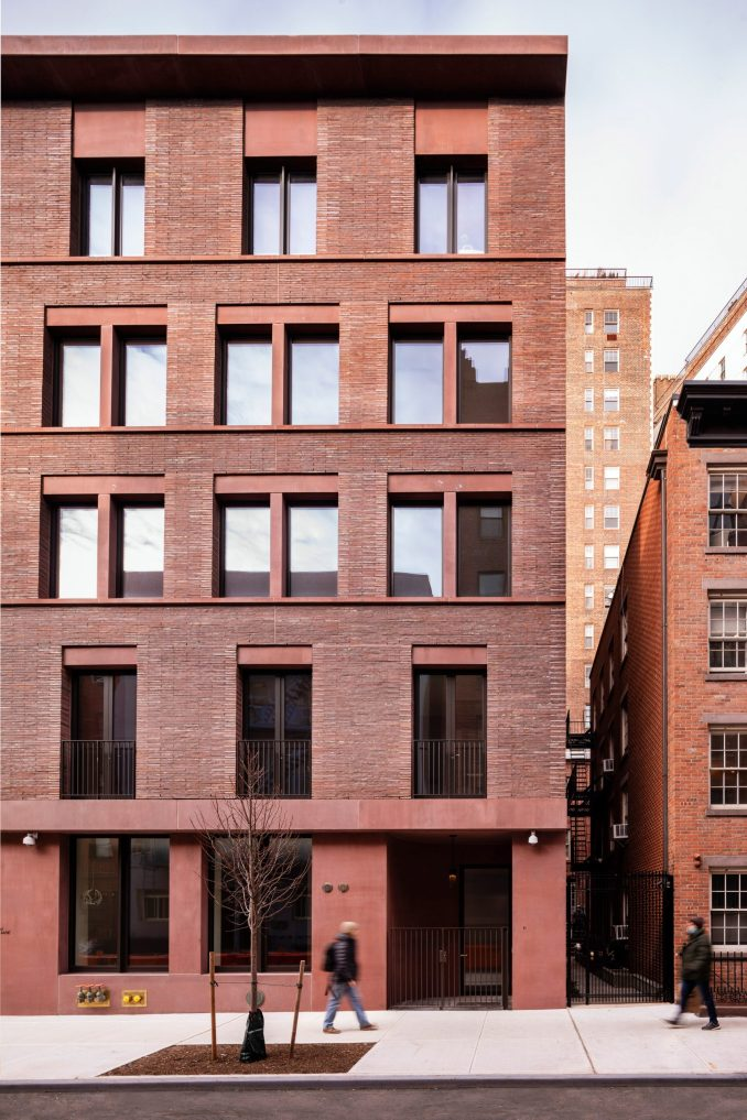 Red brick and coloured concrete facade of an apartment building