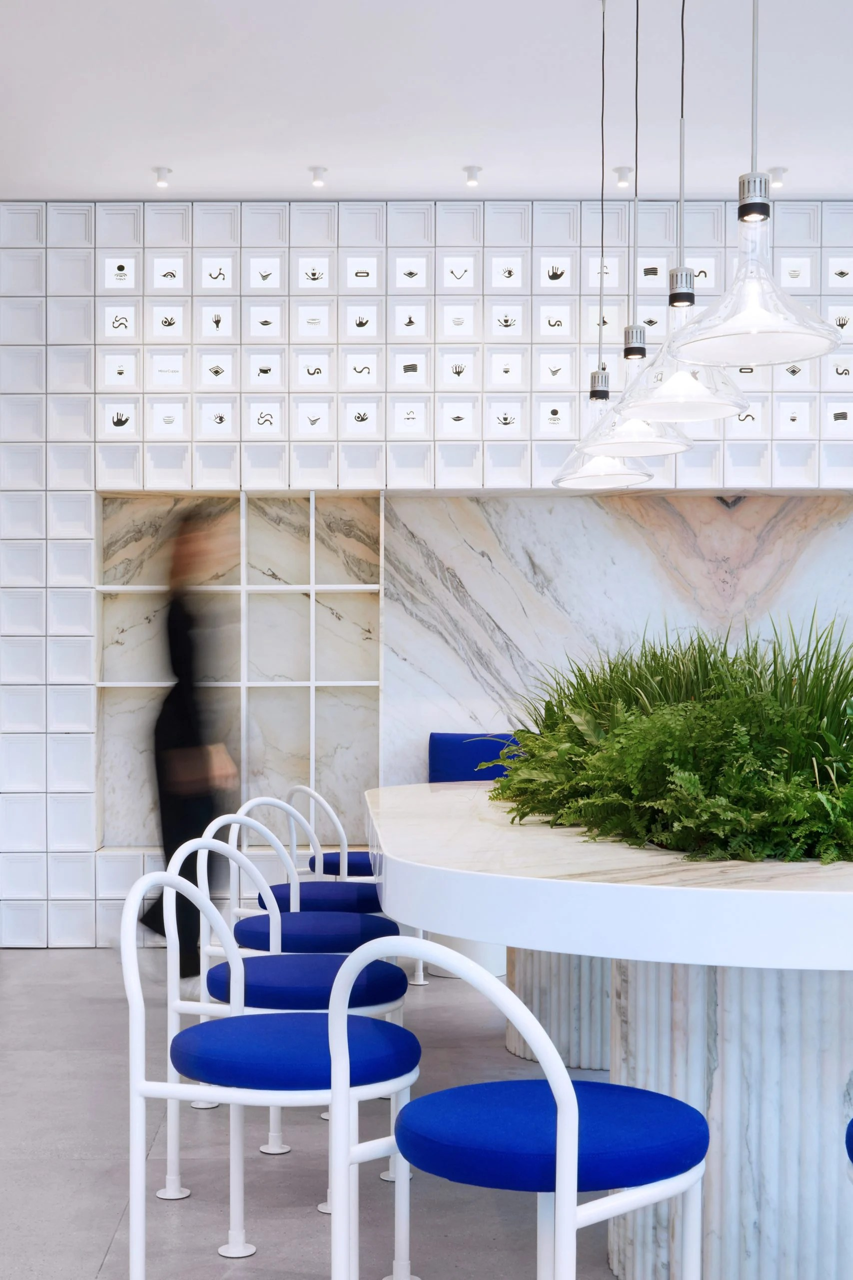 Communal table with marble top and white block wall in Mini Cuppa cafe