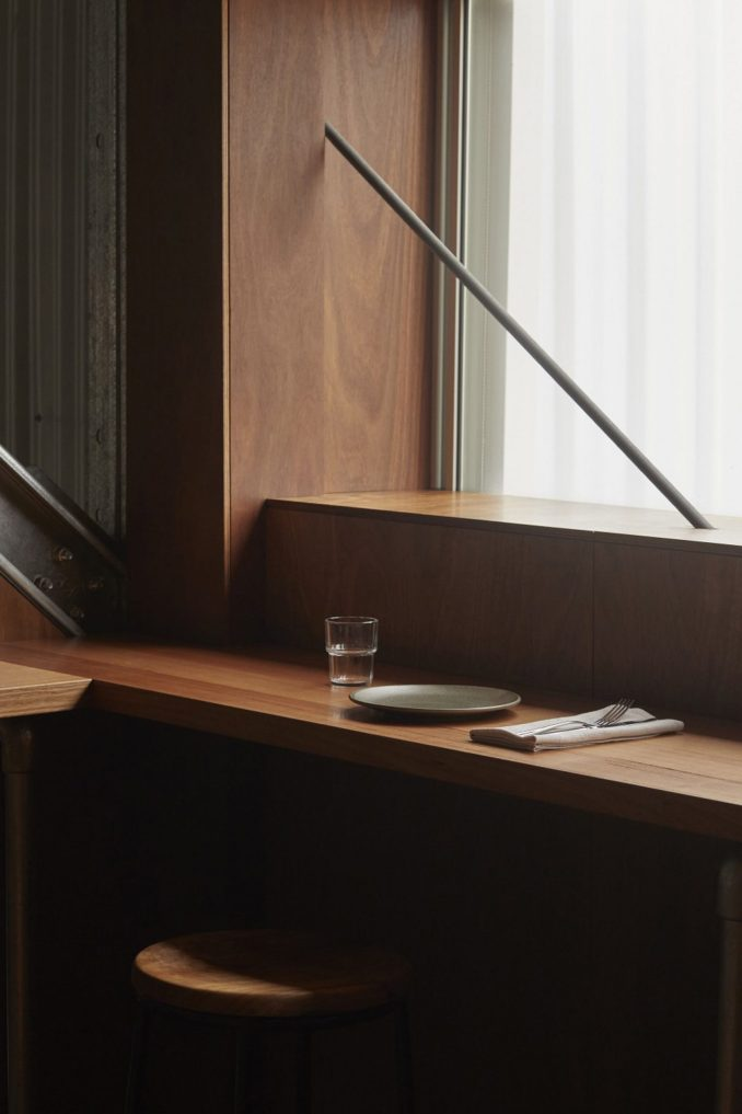 Wooden counter seating and stool in restaurant interior by Pattern