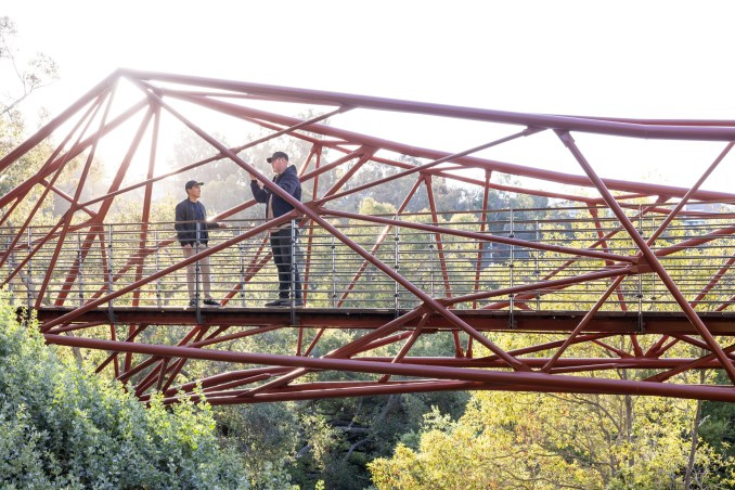 Two people stand on a bridge across a canyon