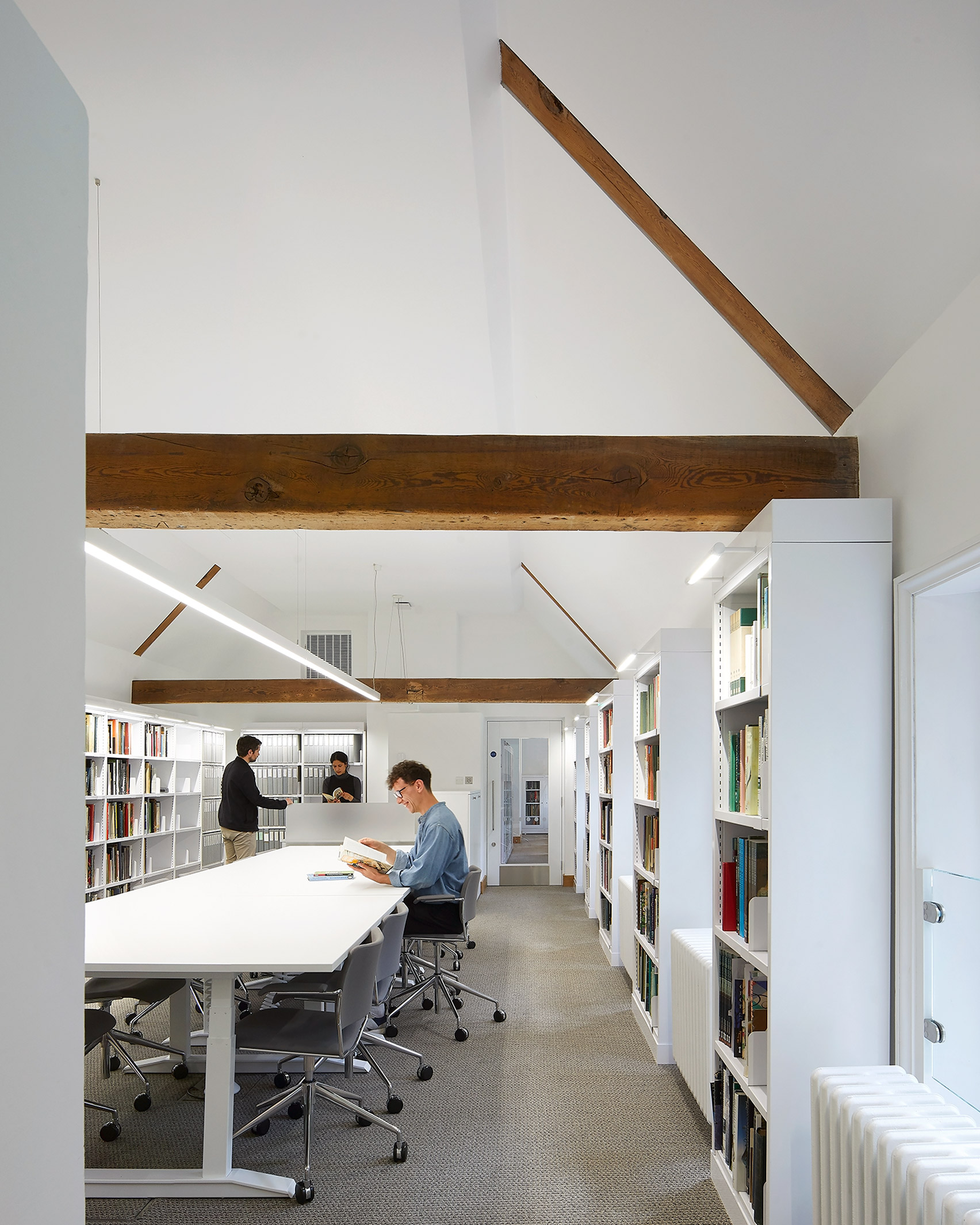 A white-walled library with exposed wooden beams