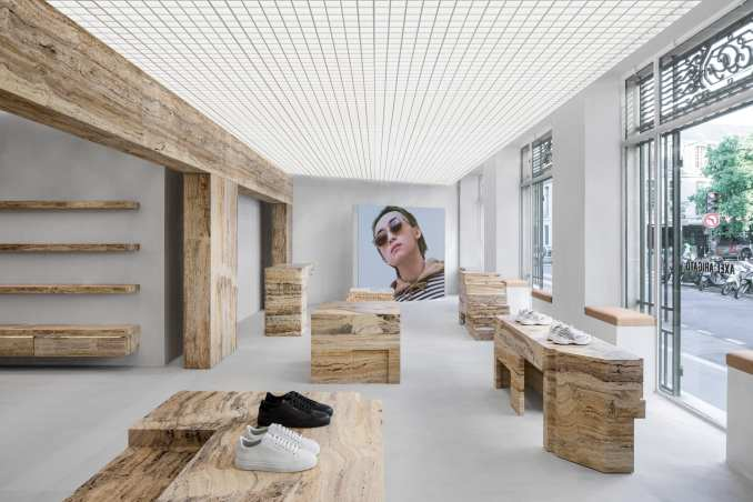 Retail interior by Halleroed with shoes displayed on travertine blocks