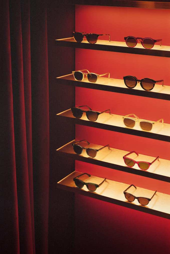 Acryclic glasses display with red velvet curtain in eyewear store by Child Studio