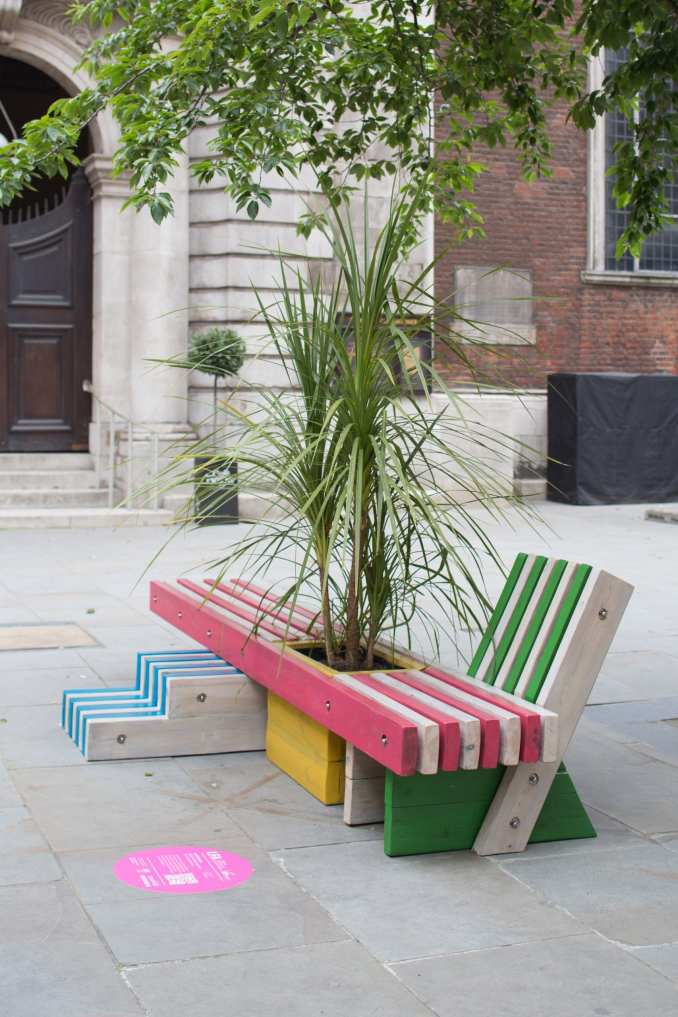 A wooden bench with a central planter