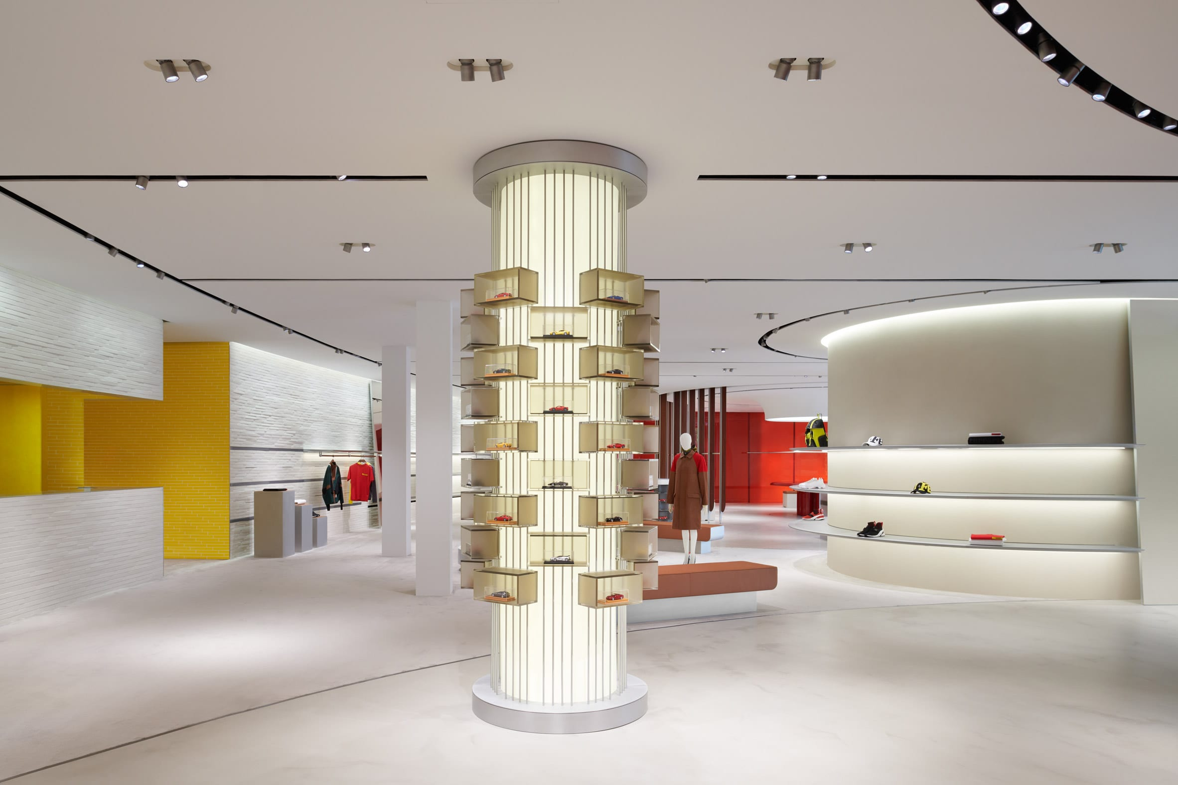 Cylindrical column displaying miniature Ferrari care in Maranello store interior