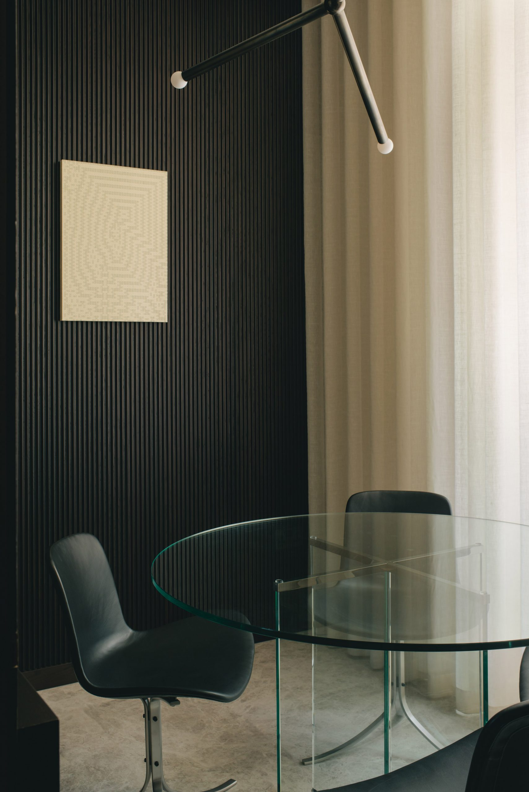 Glass table with black chairs and black panelled walls in Mandeville Place office