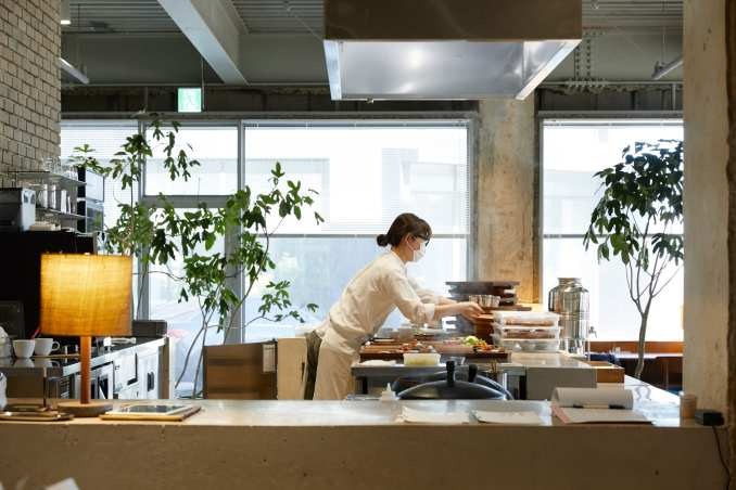 A dining space has an open kitchen at D&Department store