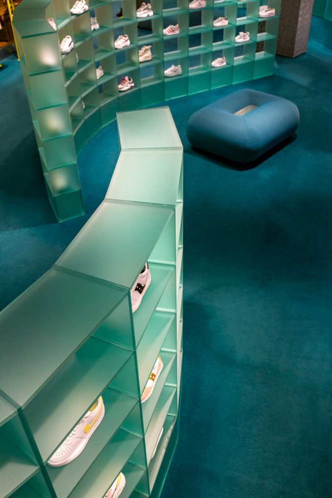 Curved plexiglass shelving displaying trainers on blue carpet in retail interior by Studiopepe