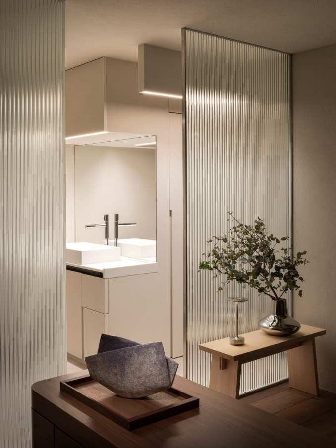 Bathroom entrance with glass walls and decorative vases in The Life concept apartment