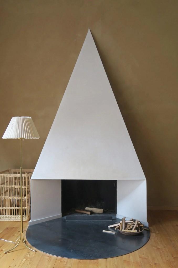 Pointy white fireplace in front of brown wall in interior by Philipp von Matt