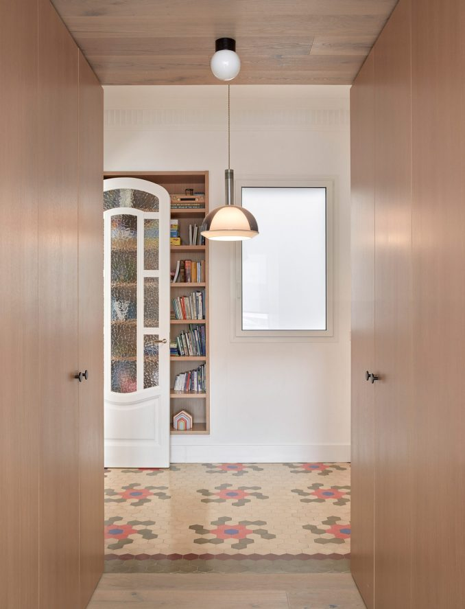 Wooden bookcase franked by wardrobes in interior by DG Arquitecto
