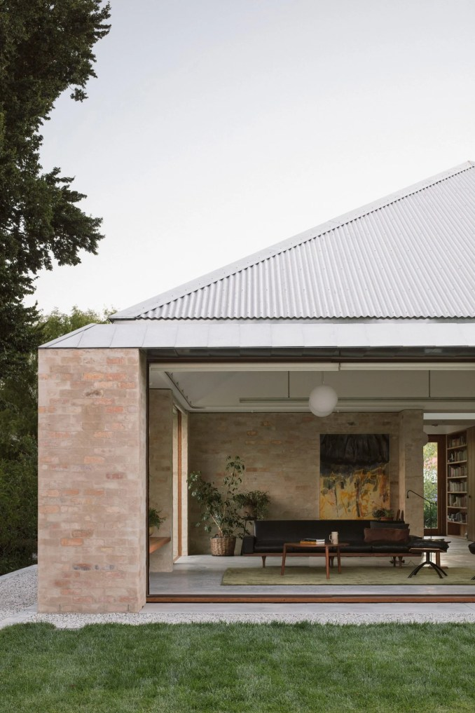 A brick house with a corrugated steel roof
