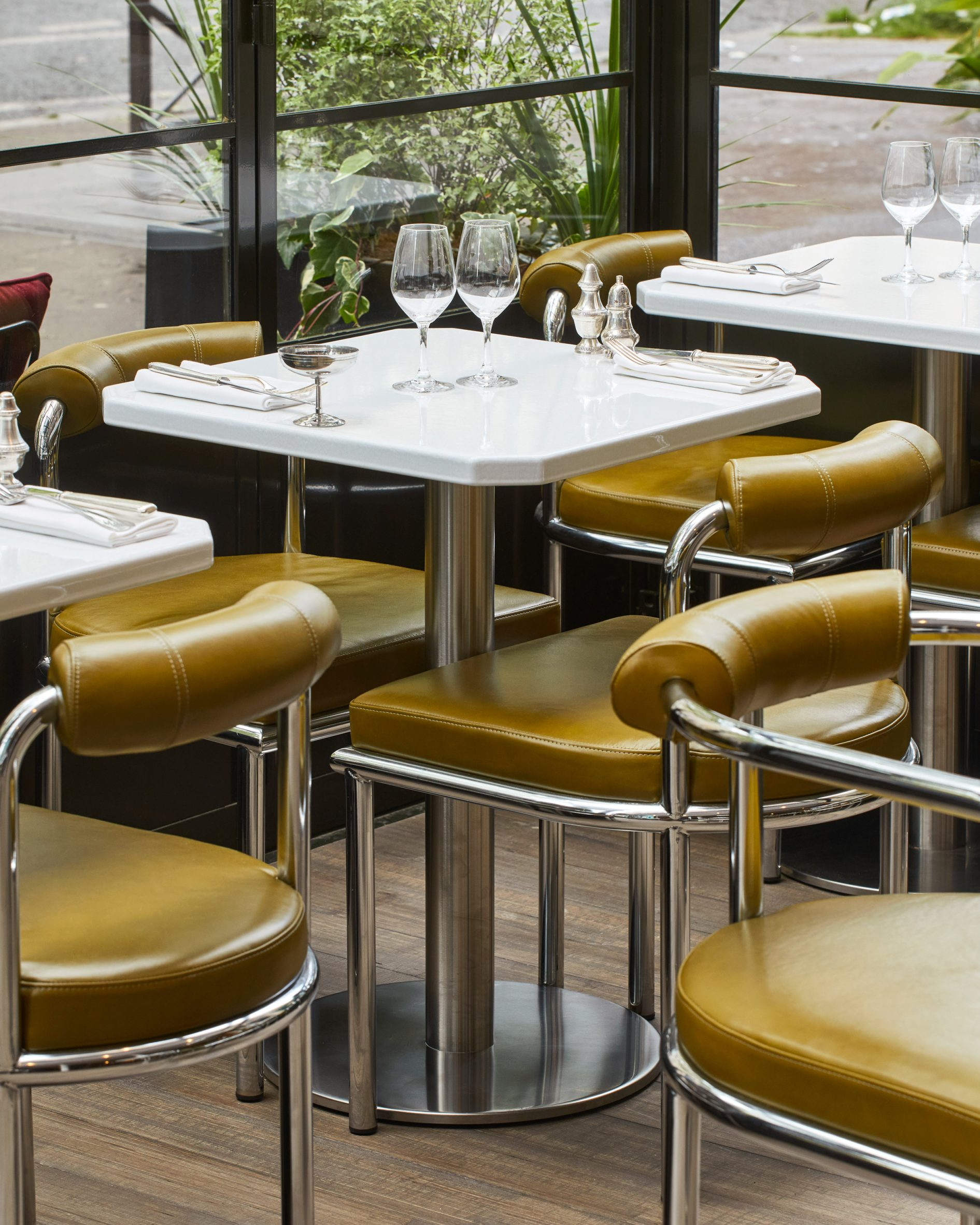 Tubular steel and green leather chairs in Abstinence restaurant interior