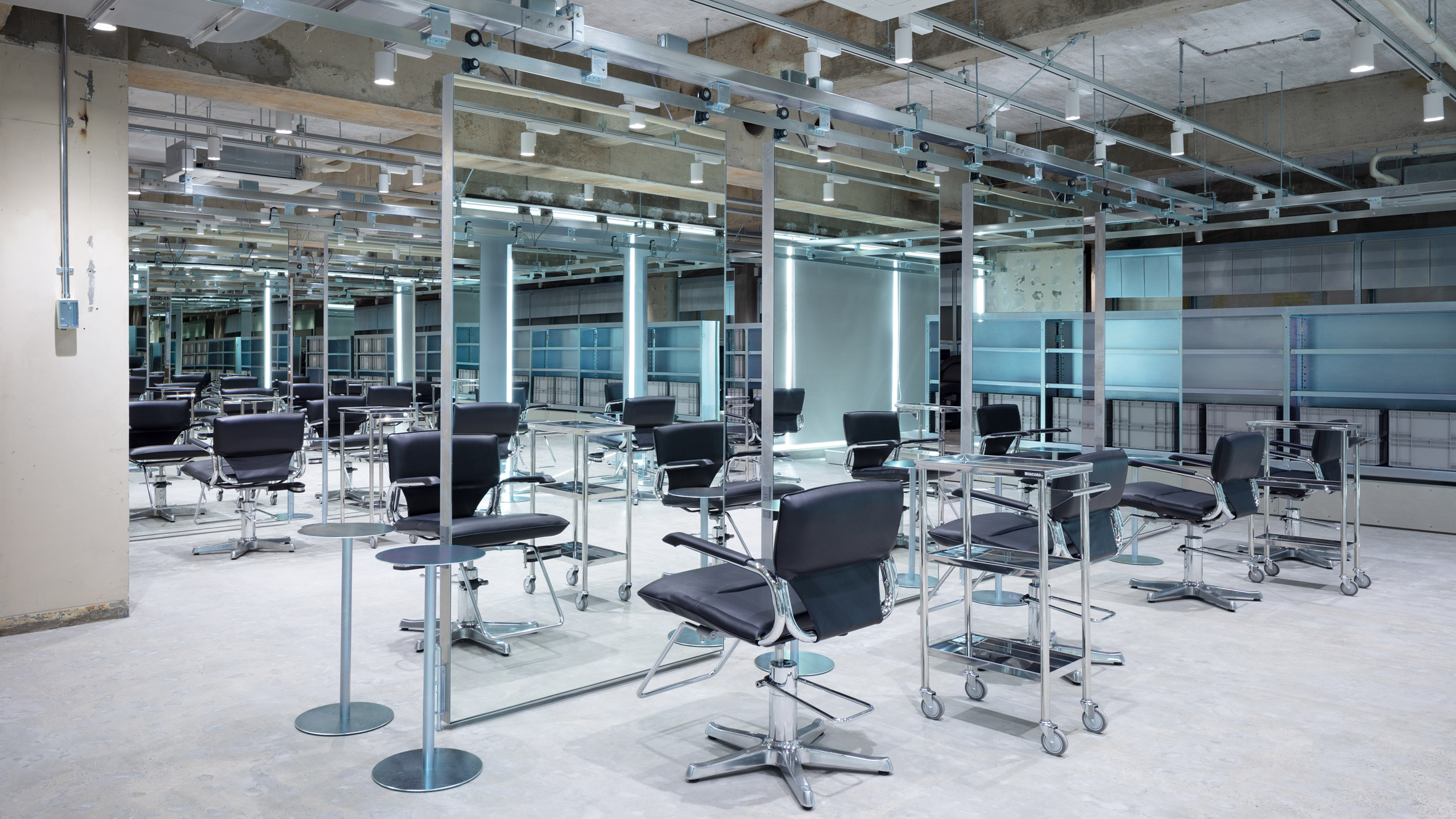 Hair styling units with suspended mirrors and leather and steel chairs by Schemata Architects