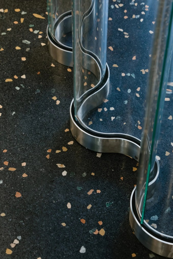 Terrazzo floor with wavy clear dividing wall in Off-White Paris store