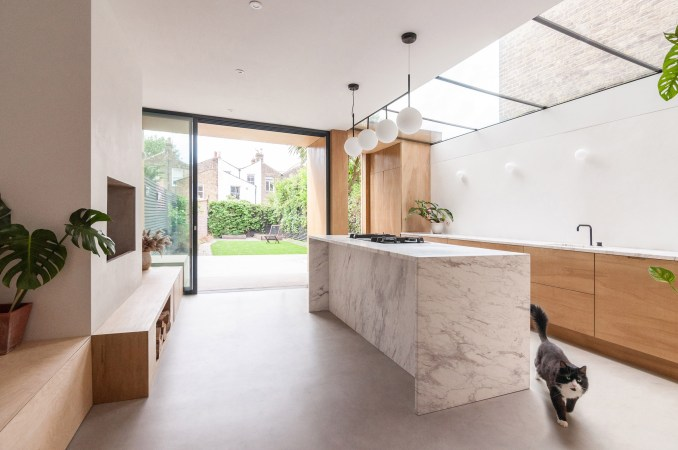 A kitchen with a marble island and wooden cabinetry