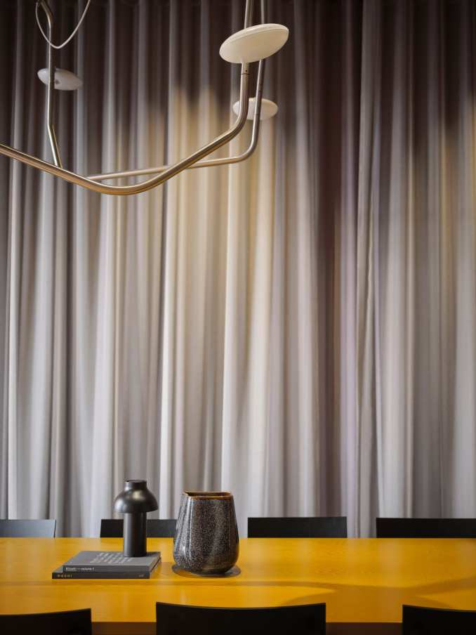 Grey curtains contrast with the yellow table