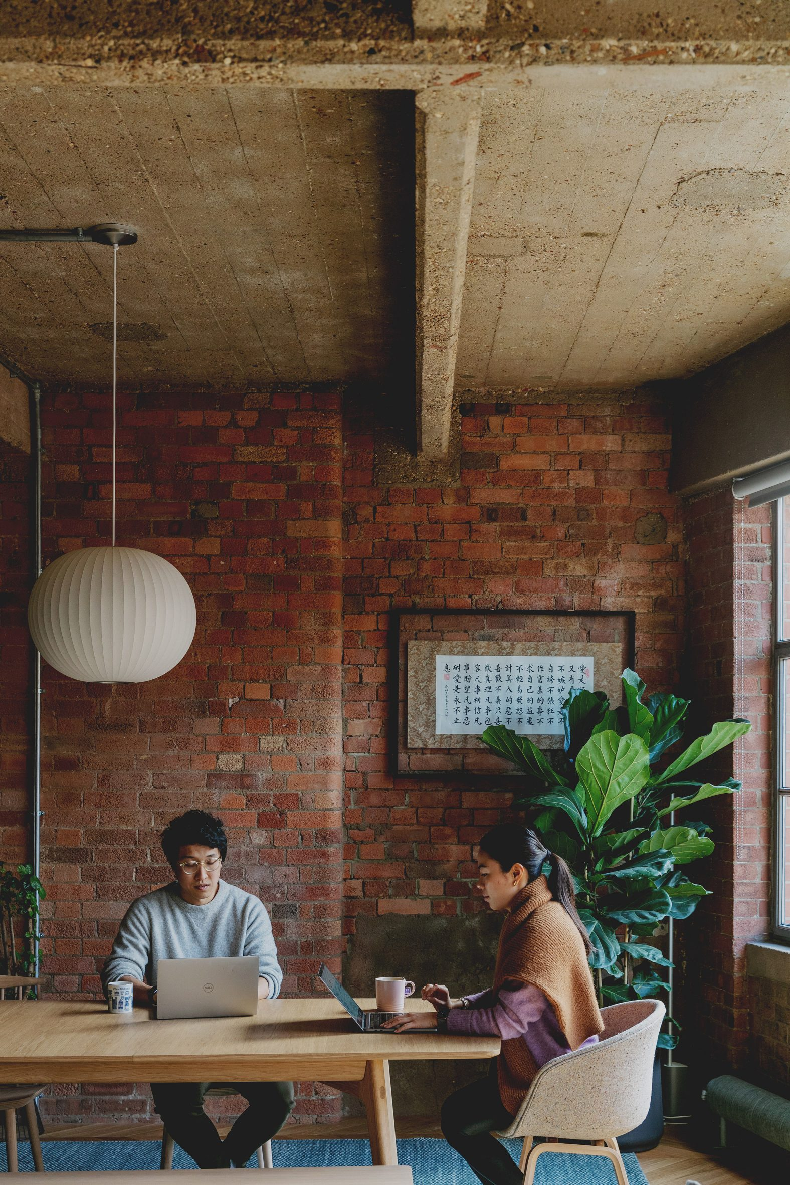 Mike and Jen at the dining table in St John Street warehouse apartment by Emil Eve Architects