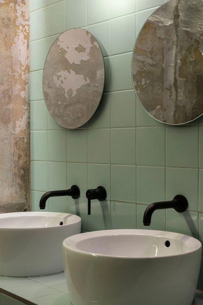 Bathroom with mint green tiles and exposed concrete