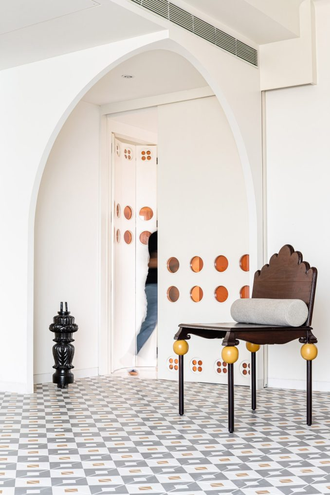 Curved walls and mosaic floors leading to temple in Mumbai apartment