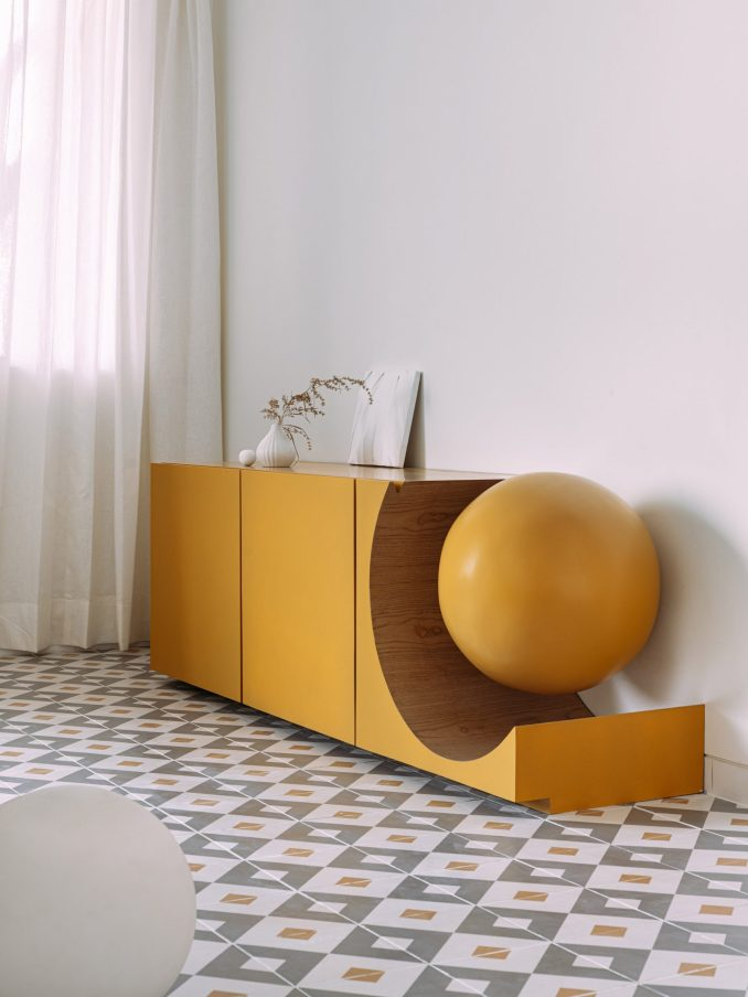 Mustard yellow cupboard with sphere cutout in interior by The Act of Quad