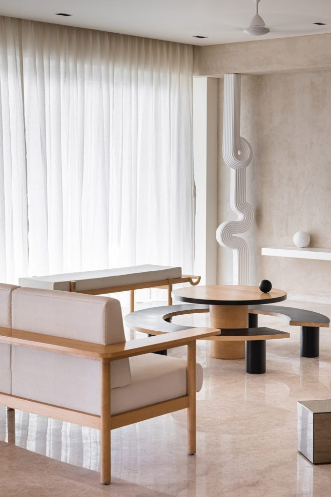 Sofas around a round coffee table with a curved bench and a winding column in Mumbai apartment