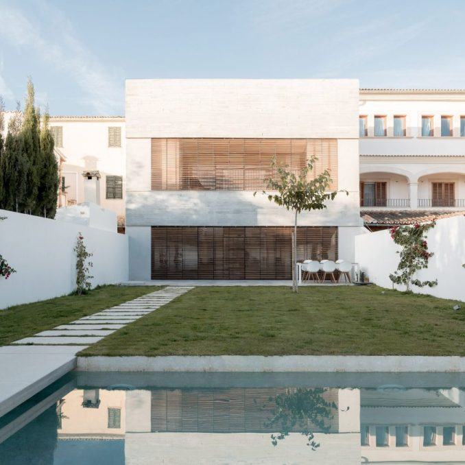 The home is surrounded by a white wall