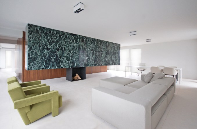A white living room with a marble partition