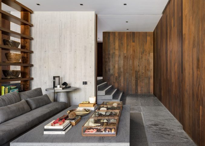 the living room by Manuel Cervantes has a concrete wall