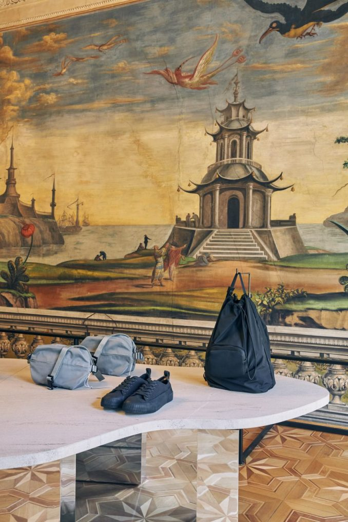 Bags and shoes displayed on stone table in front of fresco